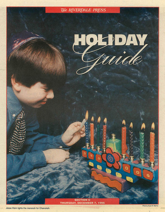 Jesse Klein lights the 7th candle on a colorful menorah.