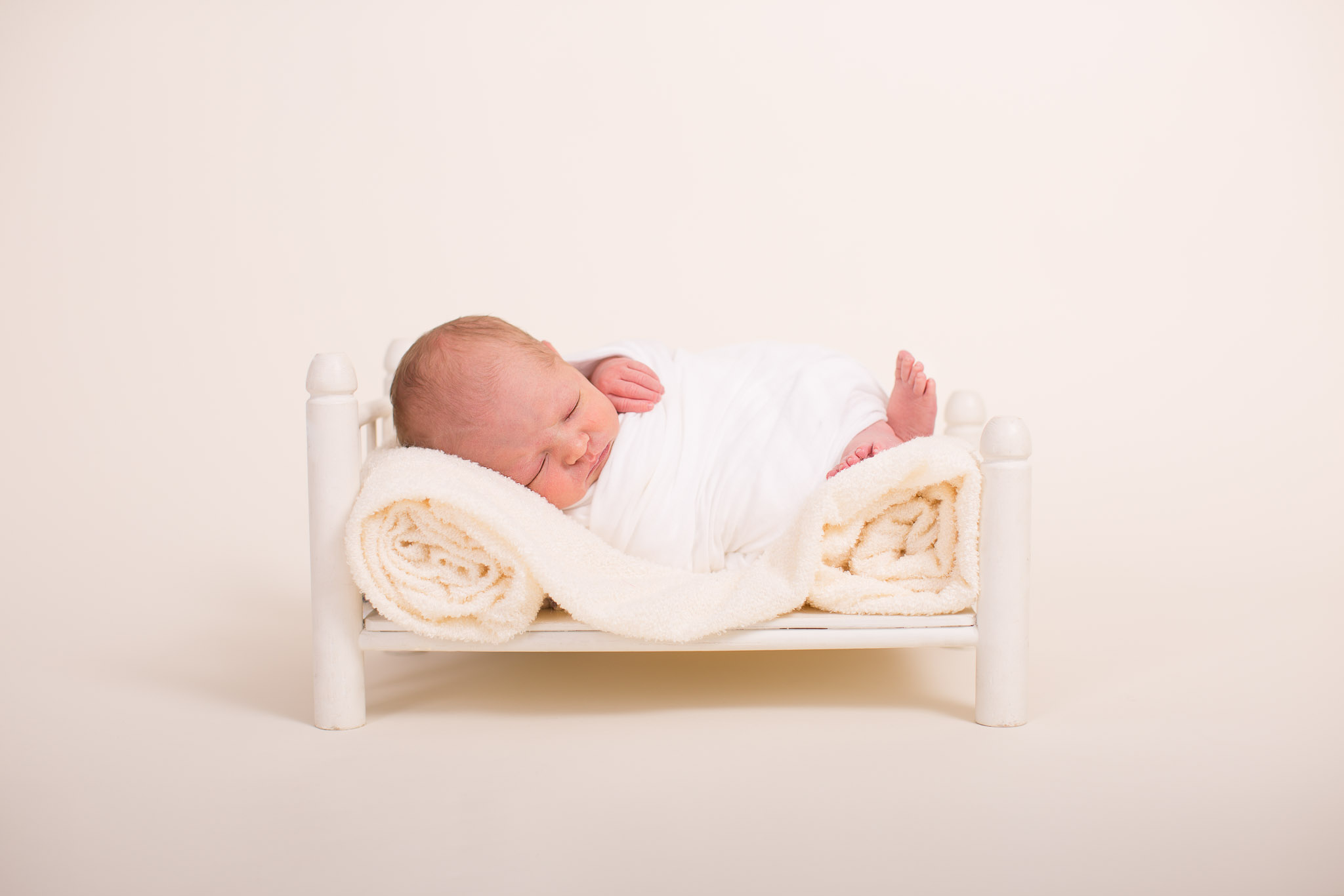 Image of baby asleep on little white prop bed