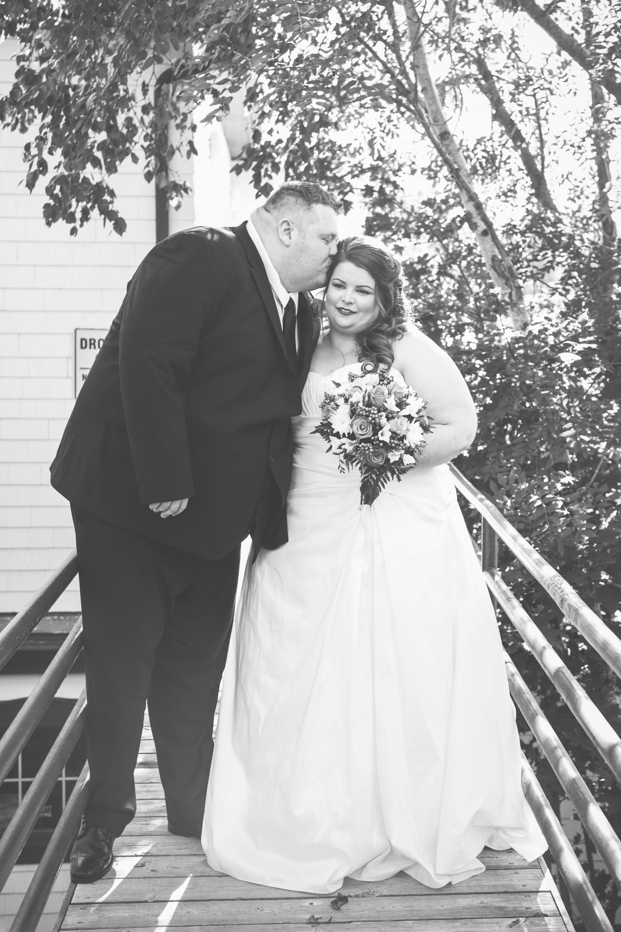 Black and white image of groom kissing bride