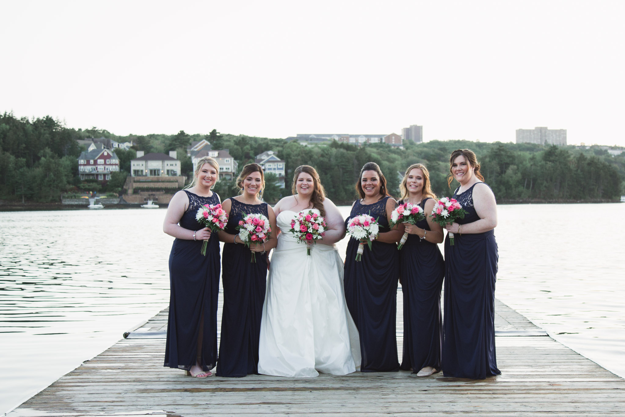 Image of bride and bridesmaids standing on the dock at Saint Mary's boat club