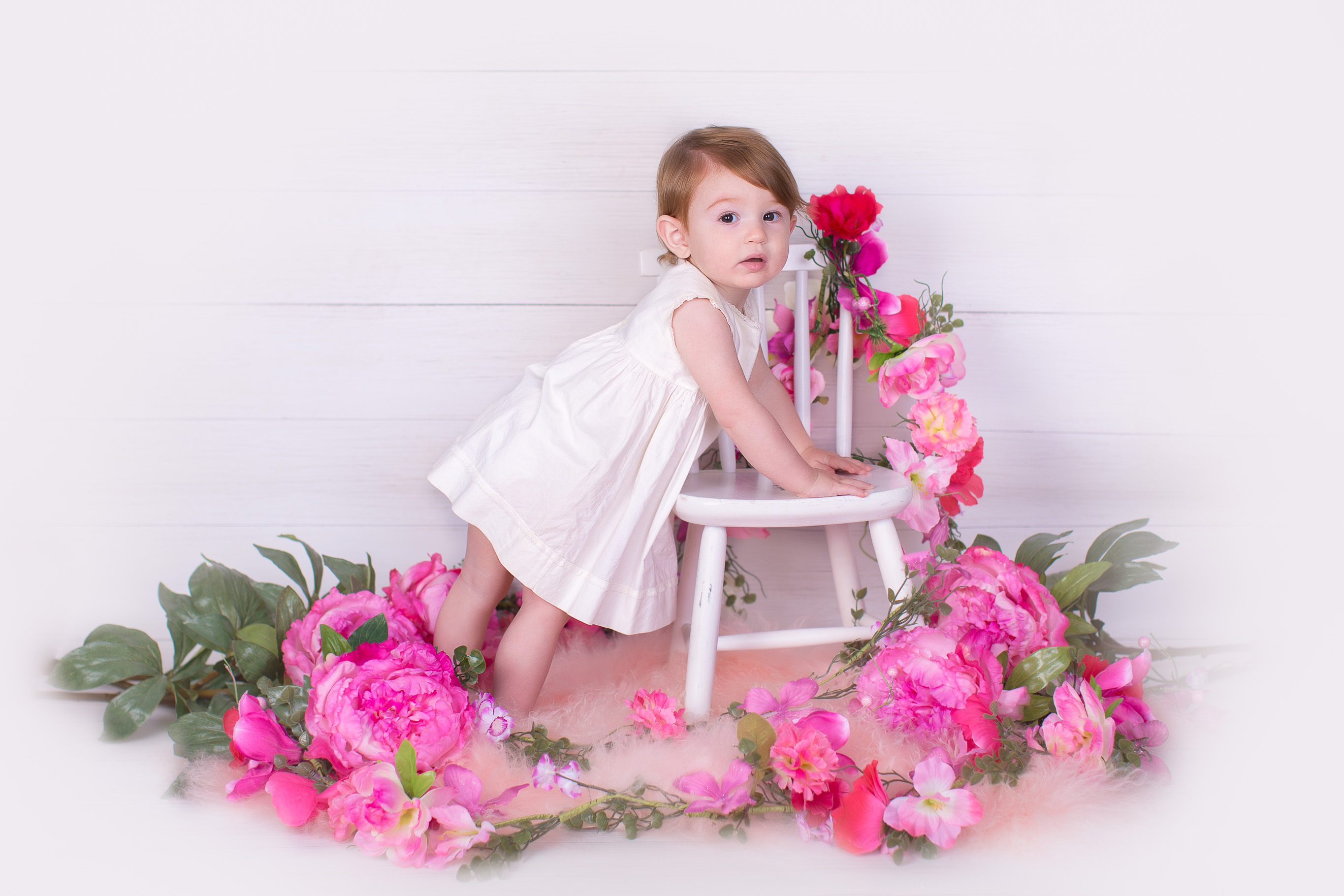 Image of one year old girl wearing white dress posing for cake smash session with pink flowers around her