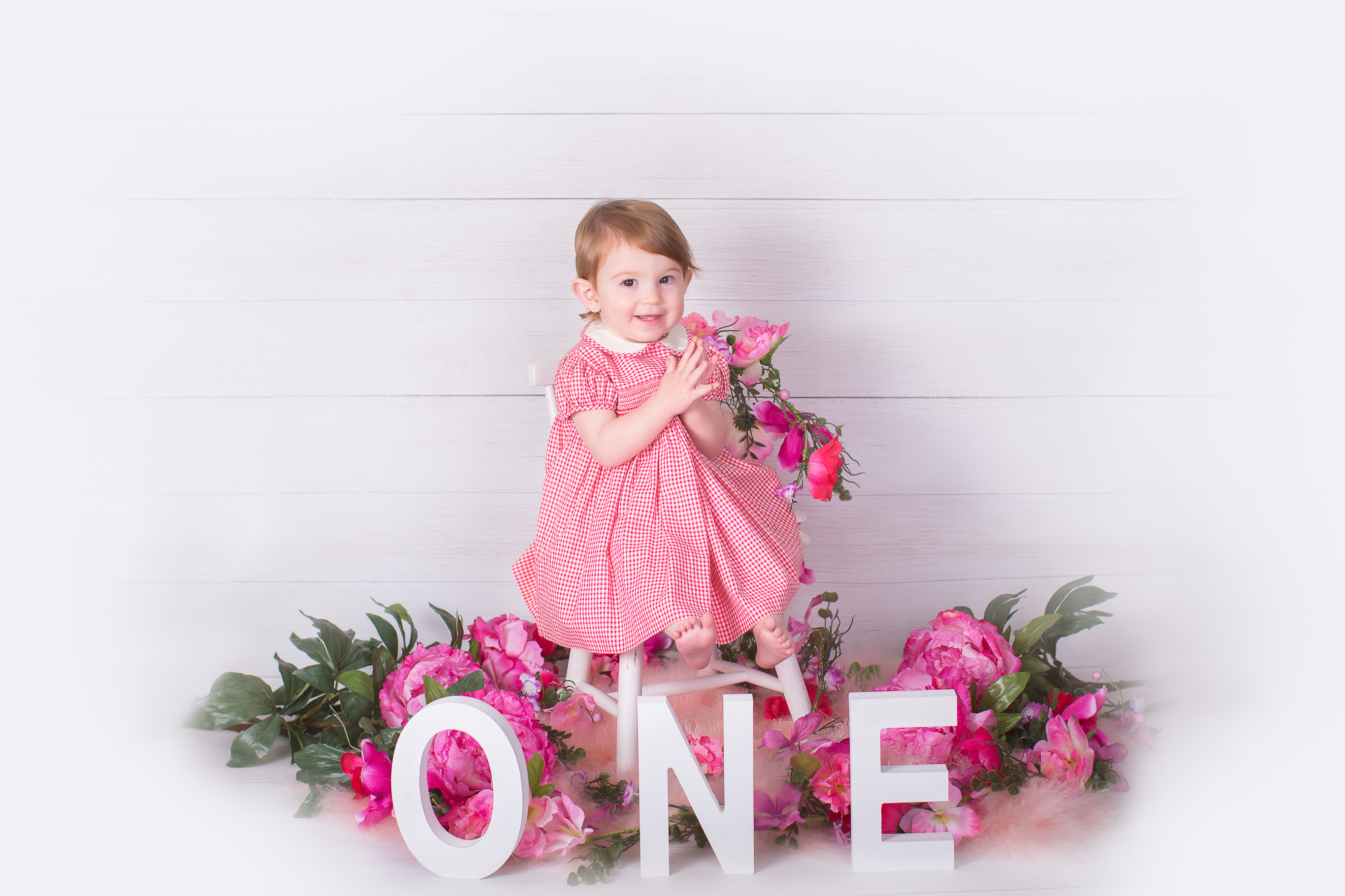 Image of one year old girl sitting gone the chair with letter spelling ONE around her