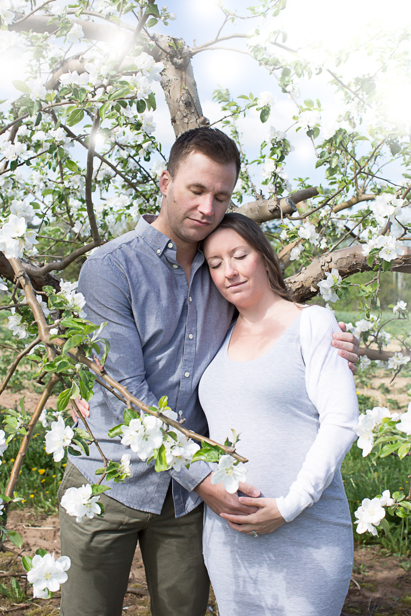 Image of expecting couple standing close with their eyes closed during apple blossom maternity session