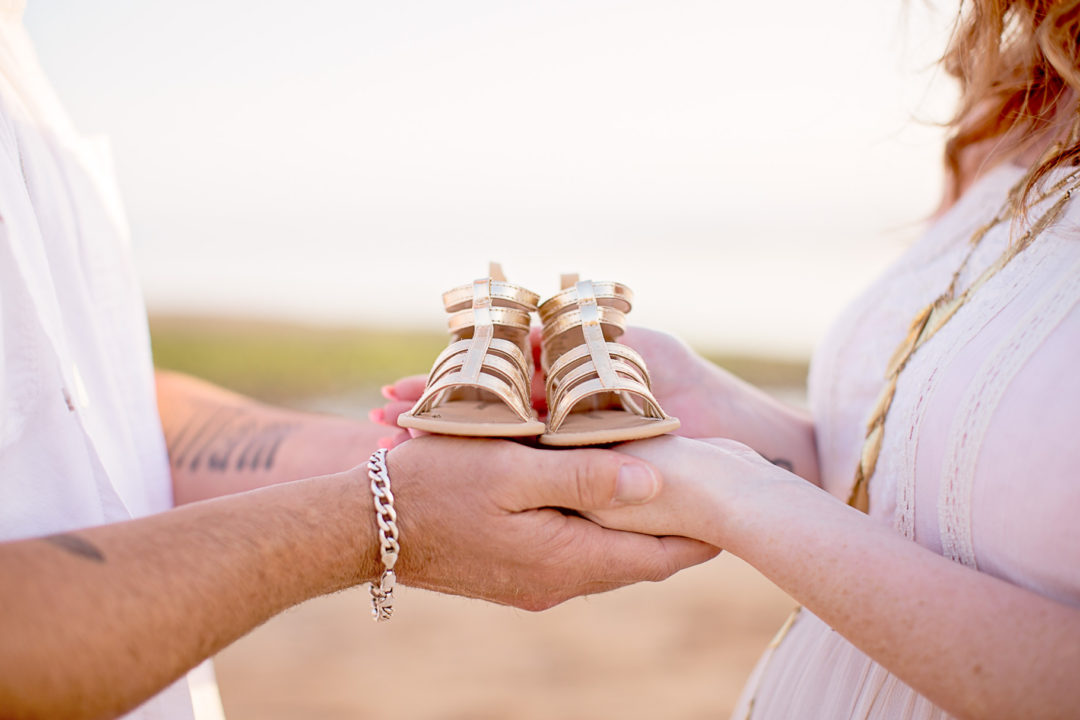 Image of expecting parents holding a gold pair of baby shoes in their hands