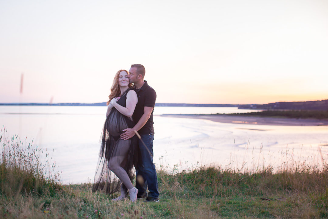 Image of expecting couple standing on the cliff overlooking the ocean