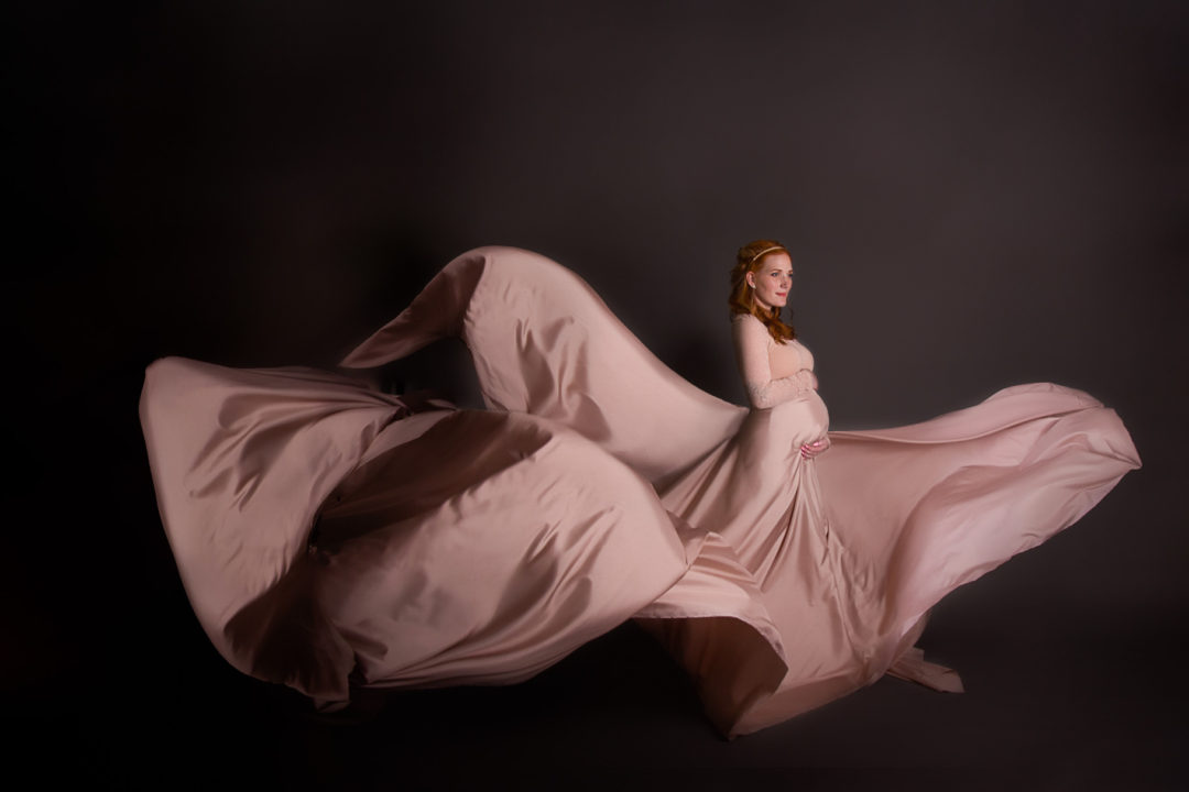 Image of studio maternity session of woman wearing beige flowing dress