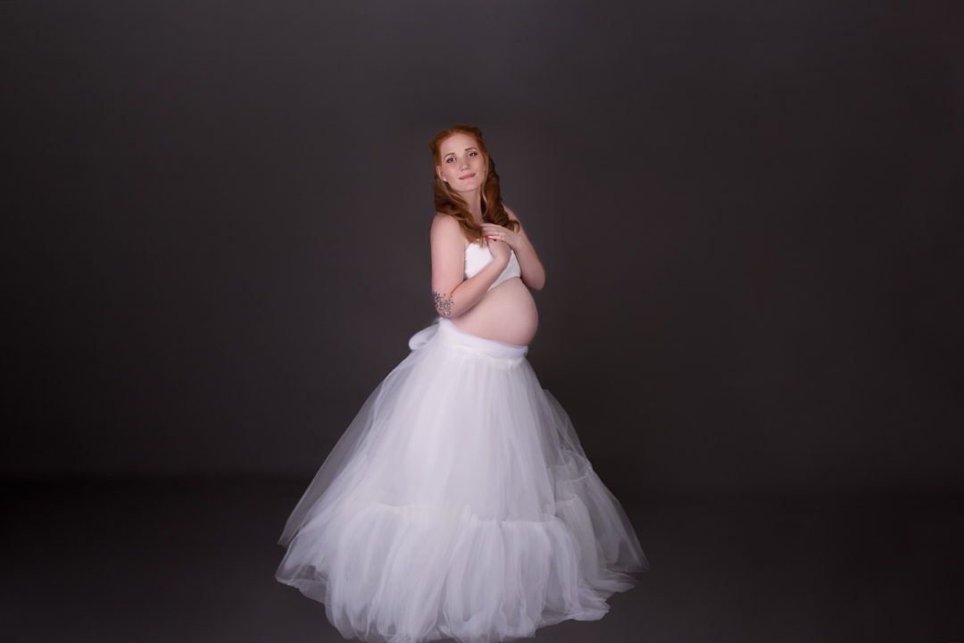 Image of pregnant woman with her hand by the chest wearing white tulle skirt