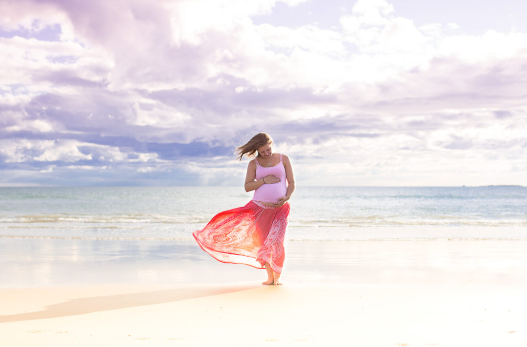 Image of woman holding her pregnant belly standing on the beach by the water