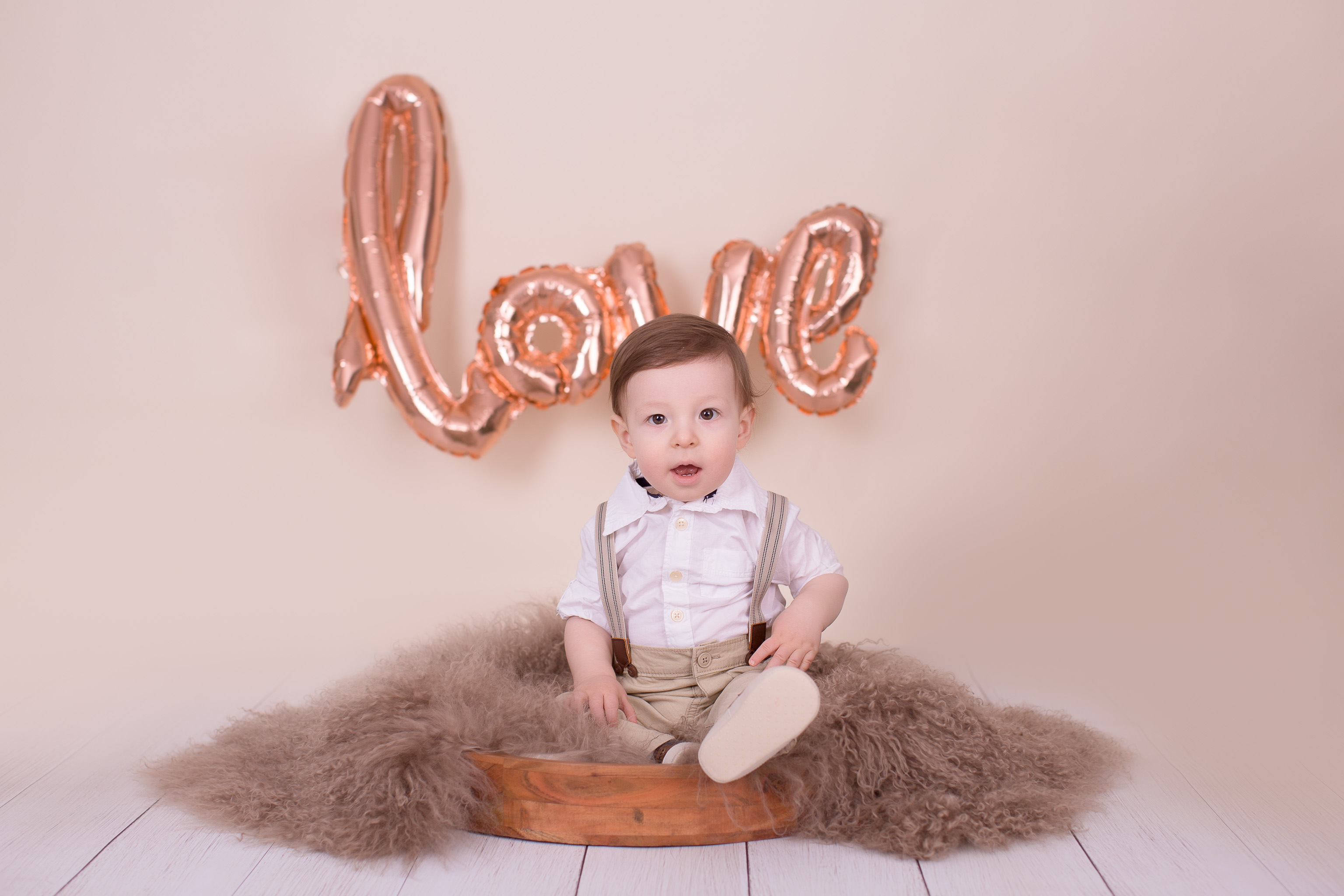 Boy posing for a session sitting in the posing bowl with word LOVE written behind him