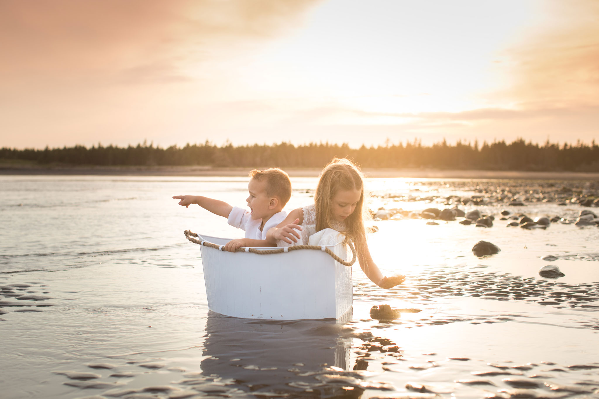 Two children playing in toy boat by the beach