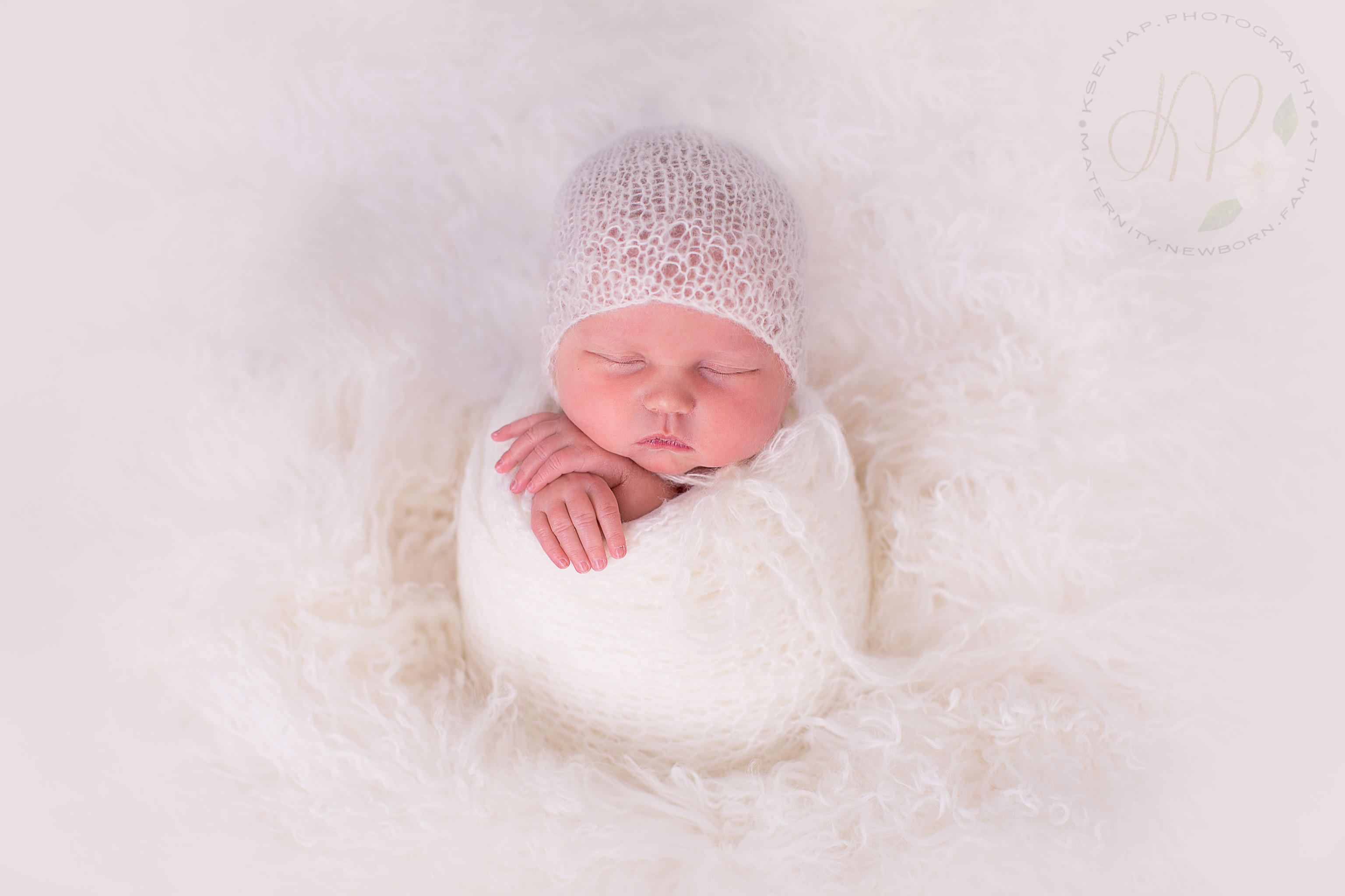 Image of newborn baby wrapped in white fabric