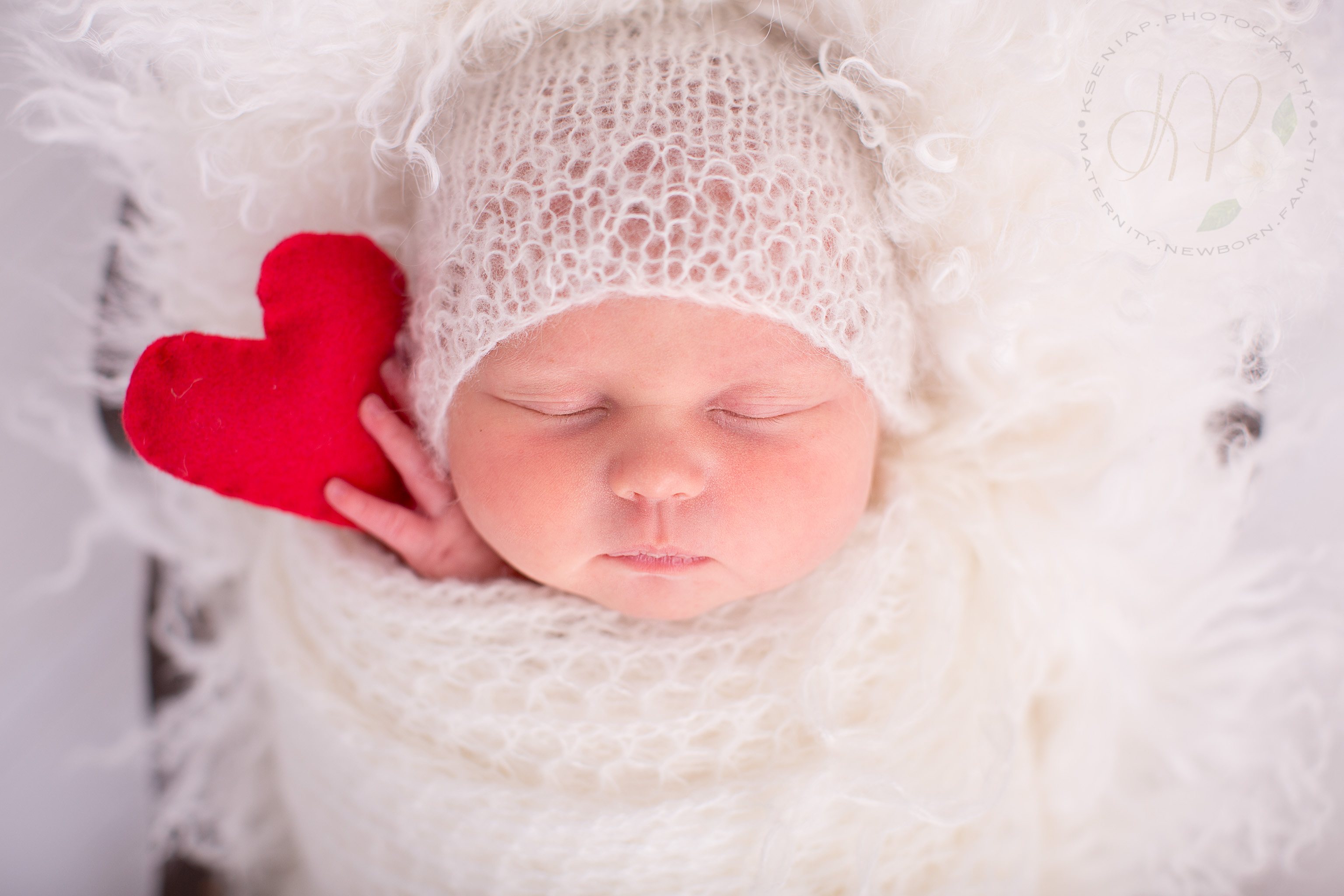 Image of newborn baby wrapped in white fabric holding felt heart