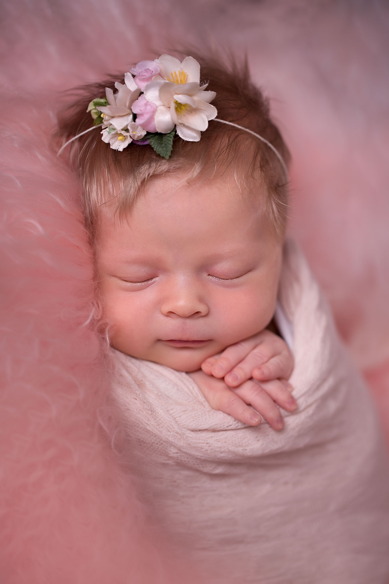 Newborn baby girl with flower headband asleep and posed for a newborn session
