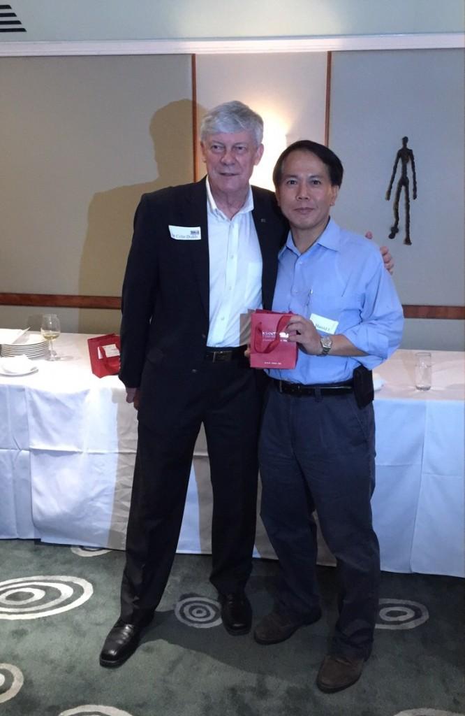 Dr. Dodds presenting a souvenir to Harold Ho.