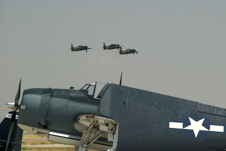 Three aerobatic F8F Bearcats fly in formation, shaming one of their less well-heeled bretheren into folding up its wings.