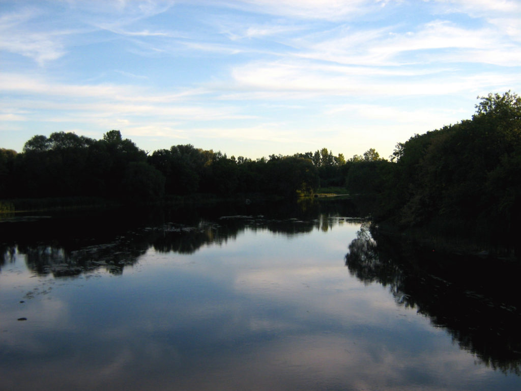 The sky reflects in the waters of the Rideau River.