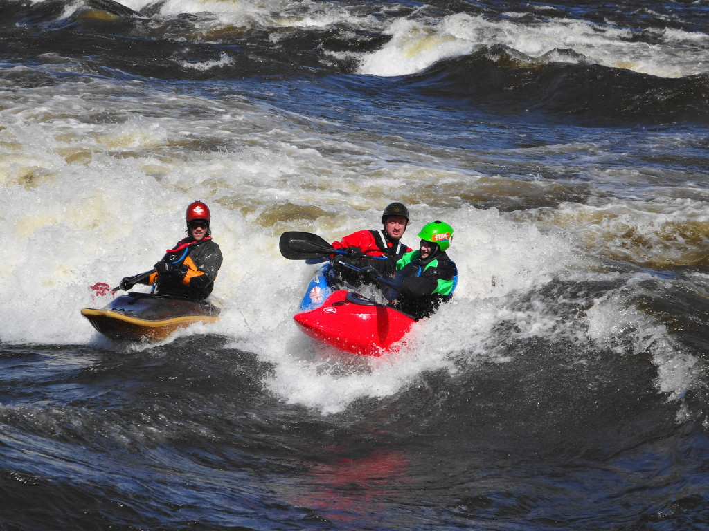 "Three kayakers jostle in friendly competition for their place on ""The Wave""."