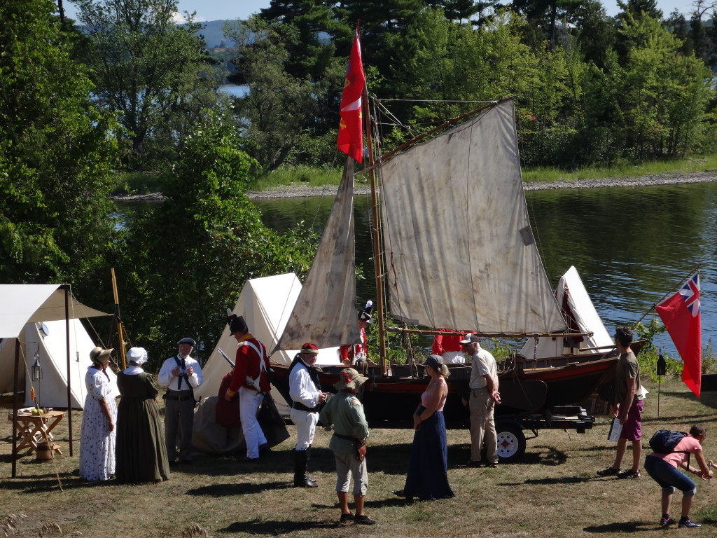 Exhibitors in period costume stand before a reconstruction of a traditional river sailboat at Riverfest at Pinhey's Point Historical Site.