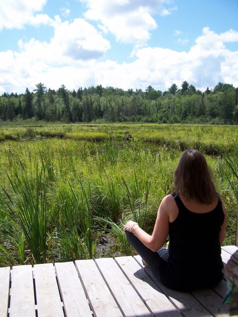 A woman meditates on a deck overlooking a wetland in the Four Seasons Conservation Forest, Deep River