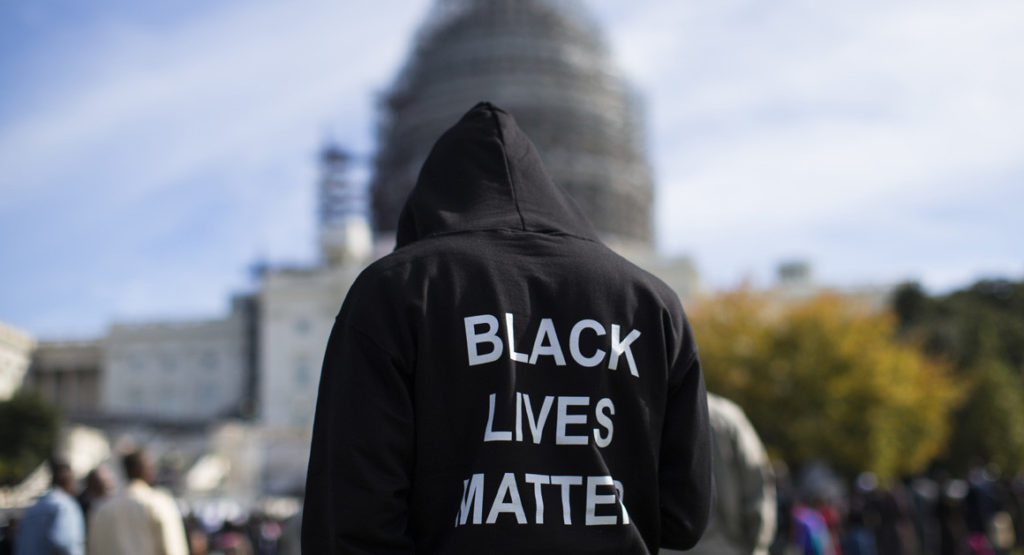 "Neal Blair wears a hoodie that reads ""Black Lives Matter"" as he stands on the lawn of the Capitol during a rally to mark the 20th anniversary of the Million Man March on Oct. 10, 2015, in Washington. 