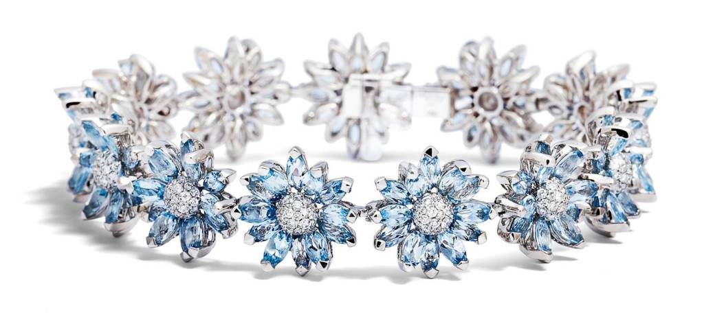 Individually set marquise stones form the petals of the daisy flower from brilliant cut diamonds and aquamarines.