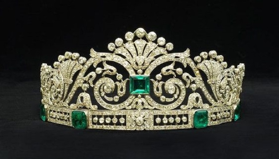 An emerald and diamond tiara in a fitted case by Marzo. The central square-cut emerald set amidst a tapering openwork panelof scrolling foliate motifs, mounted atop a band set with six graduated cut-cornered step-cut emeralds interspersed with openwork panels with knife-edge set diamond collets, the piece set throughout with old and rose-cut diamond. Circa 1915. This tiara has been in the private ownership of a Spanish aristocratic family.