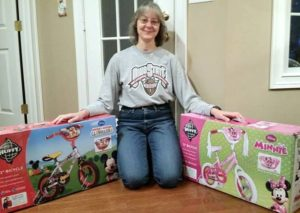 Photo of Shari with two boxed bikes. Photo by Bike Lady