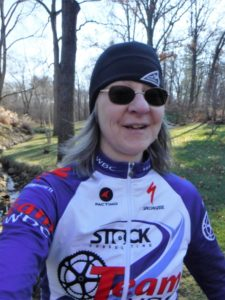 Shari stands in her bicycling jersey before the forest