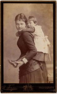 Sepia photograph, an 1880s woman wearing a dark full-length dress gives a piggy back ride to a girl wearing boots and a white apron over her dark dress.