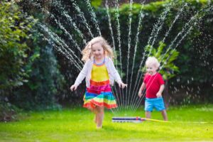 kids in the sprinkler installed in Kingwood Tx by Orions Rayne Outdoor Sprinkler Installations Company