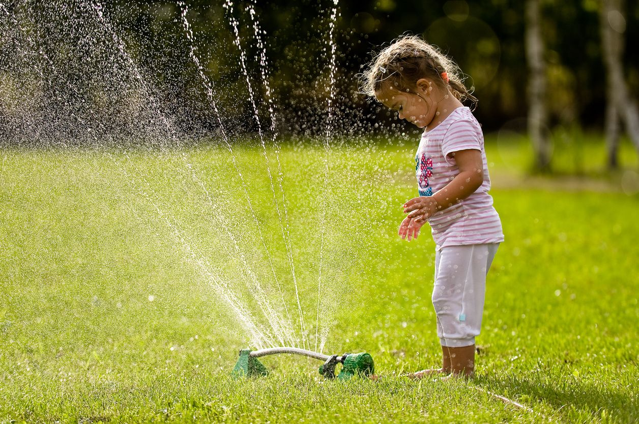 toddler looking over the top of a sprinkler
