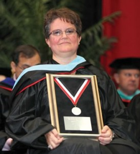 Julie Bell displays her Alumni of Distinction Award during the Spring 2013 Commencement for undergraduate and graduate candidates.