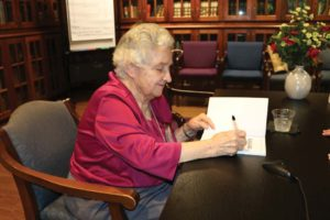 Prendergast signs a copy of her book at a reading and book signing on the UIW campus.