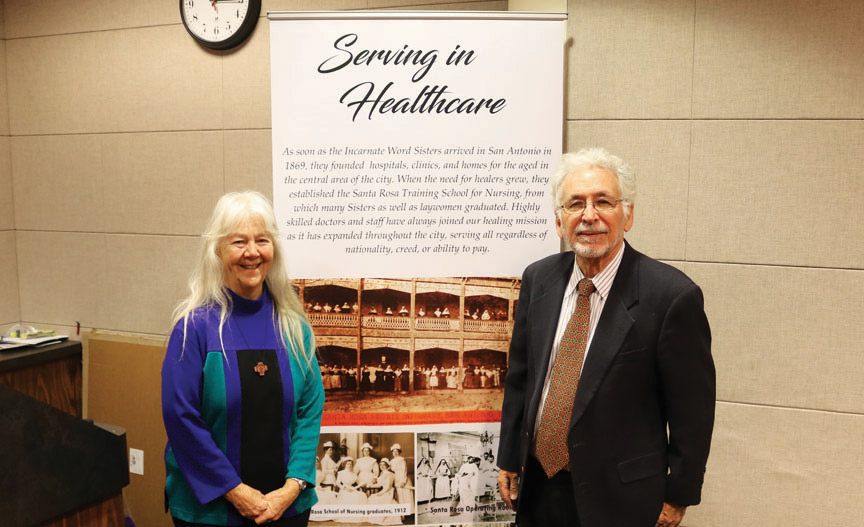 Sr. Martha Ann Kirk, CCVI, and Dr. Gilberto Hinojosa present one of the photo panels from a traveling exhibit of CCVI history.