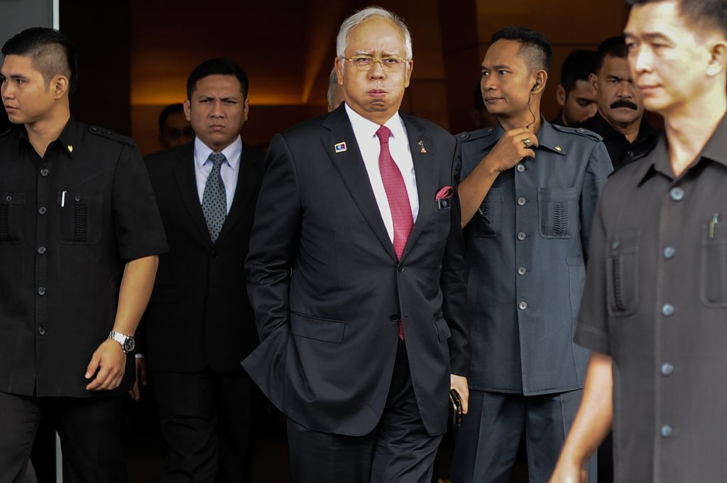 """Malaysia's Prime Minister Najib Razak (C) reacts as he walks towards his car after attending a parliament session in Kuala Lumpur on January 26, 2016. The Saudi royal family was the source of a 681 million USD """"donation"""" that has engulfed Malaysian Prime Minister Najib Razak in scandal, his attorney general said on January 26, in a statement clearing the premier of graft allegations. AFP PHOTO / MOHD RASFAN / AFP / MOHD RASFAN (Photo credit should read MOHD RASFAN/AFP/Getty Images)"""