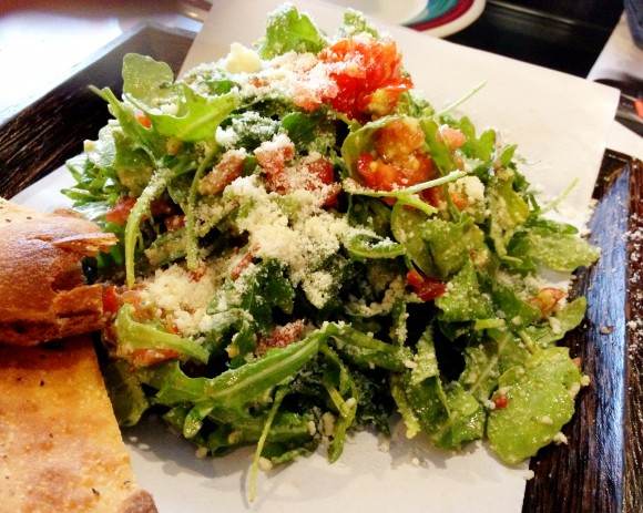 arugula and cherry tomato salad in pesto sauce with parmesan