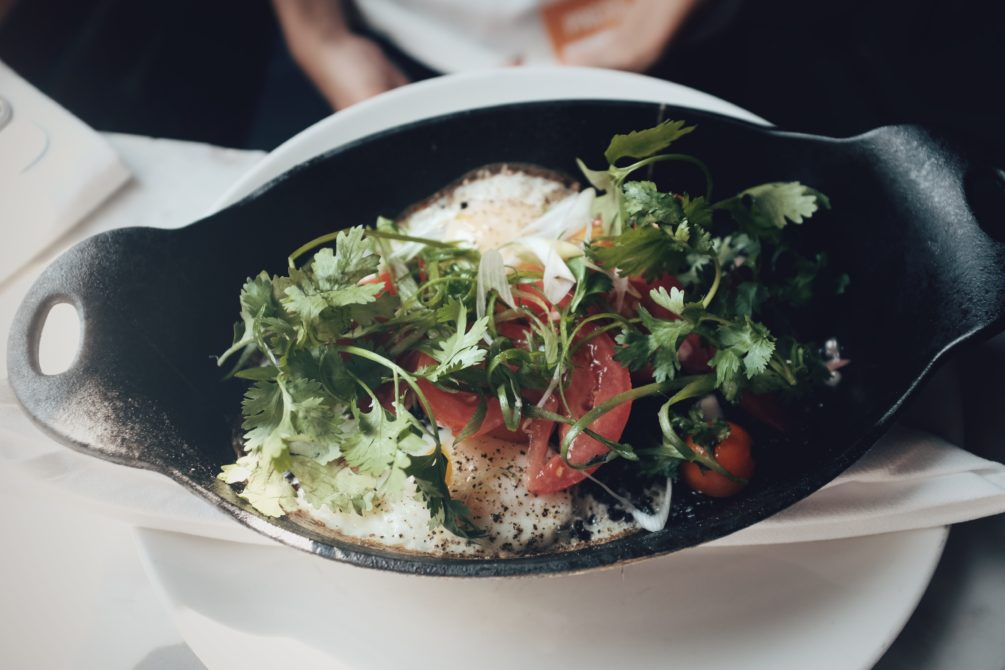 baked eggs with crispy black rice, curry and heirloom tomato