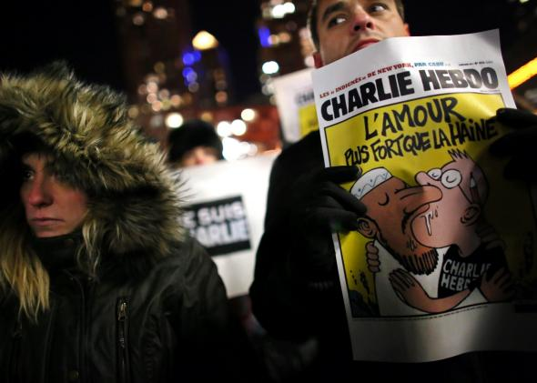 """At a memorial in New York City's Union Square, a Charlie Hebdo cover that reads """"Love is stronger than hate."""""""