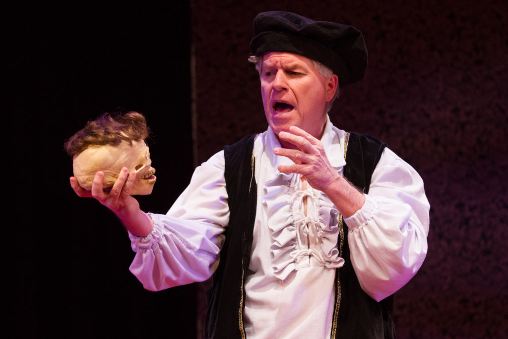 """Toupee, or not toupee?"" asks the Prince of Demark (Austin Tichenor) in the Reduced Shakespeare Company's William Shakespeare's Long Lost First Play (abridged), at Folger Theatre, April 21 – May 8, 2016. Photo by Teresa Wood."