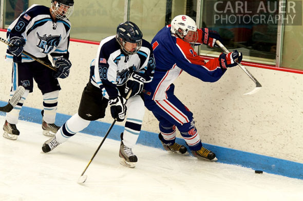 December 18, 2012: A Ralston Valley hockey player and a Cherry Creek player trie to get the puck in the game between Cherry Creek and Ralston Valley at the APEX Ice Arena on Tuesday night.