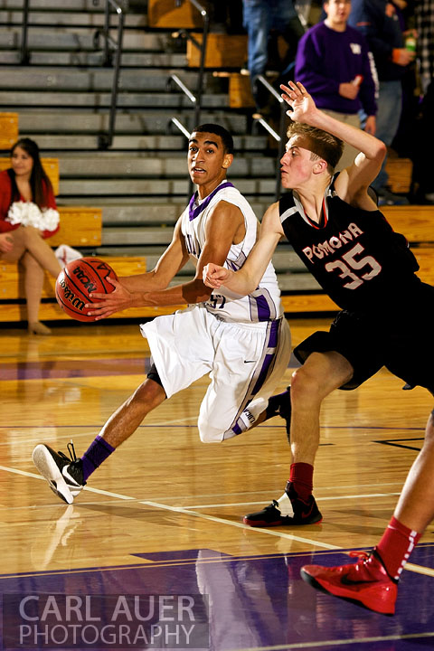 December 20, 2012: Arvada West Wildcat sophomore guard Dhillon Greene (4) drives past Pomona Panther sophomore Ryan Ward (35) on his way to the basket in the game between Pomona and Arvada West on Thursday night at Arvada West High School.