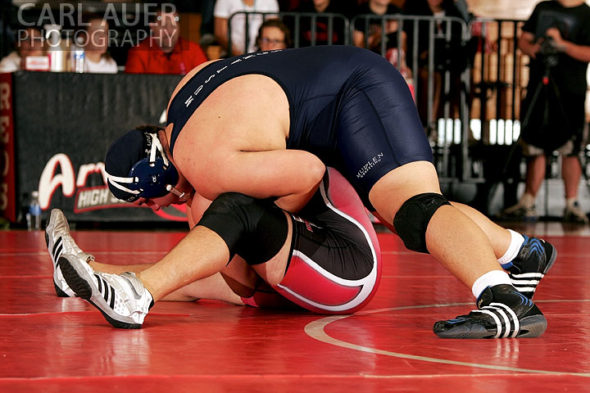 December 12th, 2012: A Mullen wrestler uses his weight to try to keep a Arvada wrestler on the mat in their meet at Arvada Senior High School