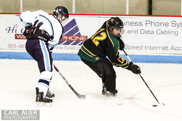 February 22, 2013: Arvada, Colorado - Bishop Machebeuf forward Brandon Gobert (12) attempts to keep the puck away from Ralston Valley Mustang junior forward Austi Resseguie in their playoff game at the Apex Center in Arvada