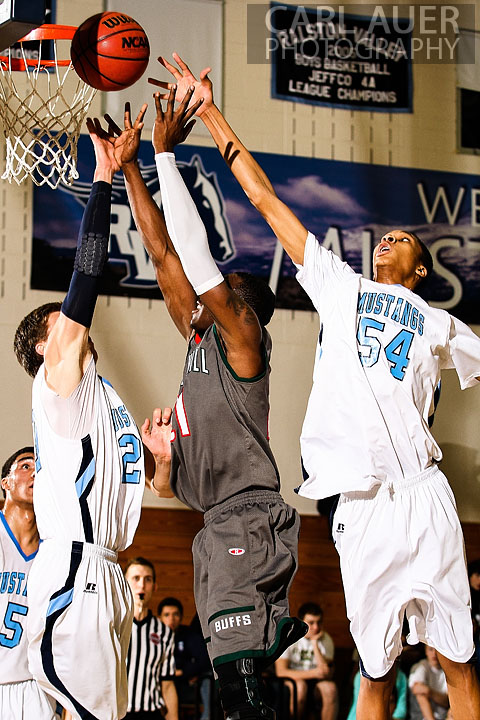 February 27th 2013: Arvada, Colorado - Smoky Hill Buffaloes Jaylen Petty (21) sneaks a shot up past the defense from Ralston Valley Mustangs freshman Dallas Walton (54) and senior Spencer Svejcar (20) in the first round state playoff game at Ralston Valley High School