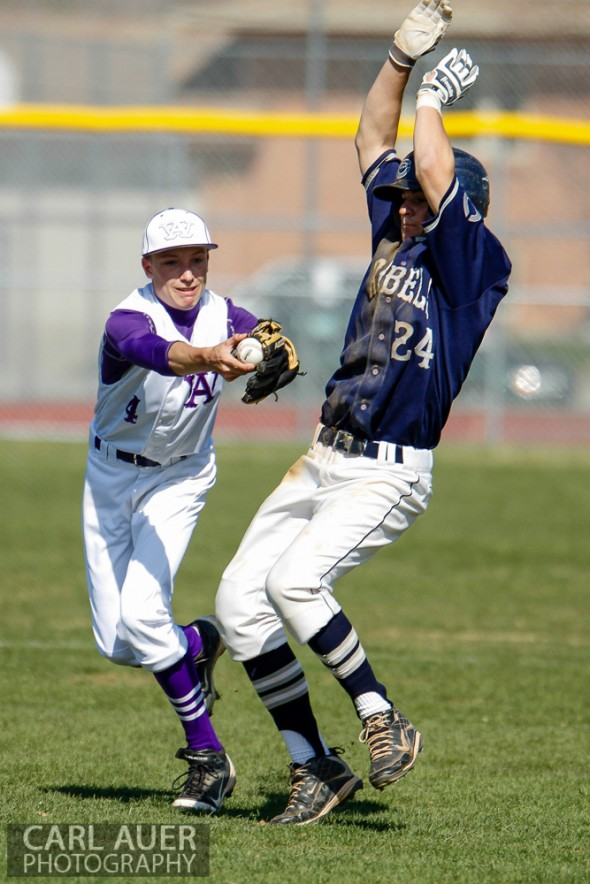 April 26th, 2013: Columbine Rebels baserunner Austin Anderson (24) avoids the tag by Arvada West Wildcat's shortstop Ethan Fleming (4) in the league game at Arvada West High School in Arvada, Colorado