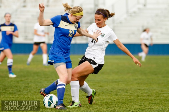 April 29th, 2013:  Wheat Ridge Farmers senior midfielder Elise Boisnard (12) stiff arms D'Evelyn Jaguars senior Kendall MacCagnan (19) in the game at the North Area Athletic Complex in Arvada, Colorado