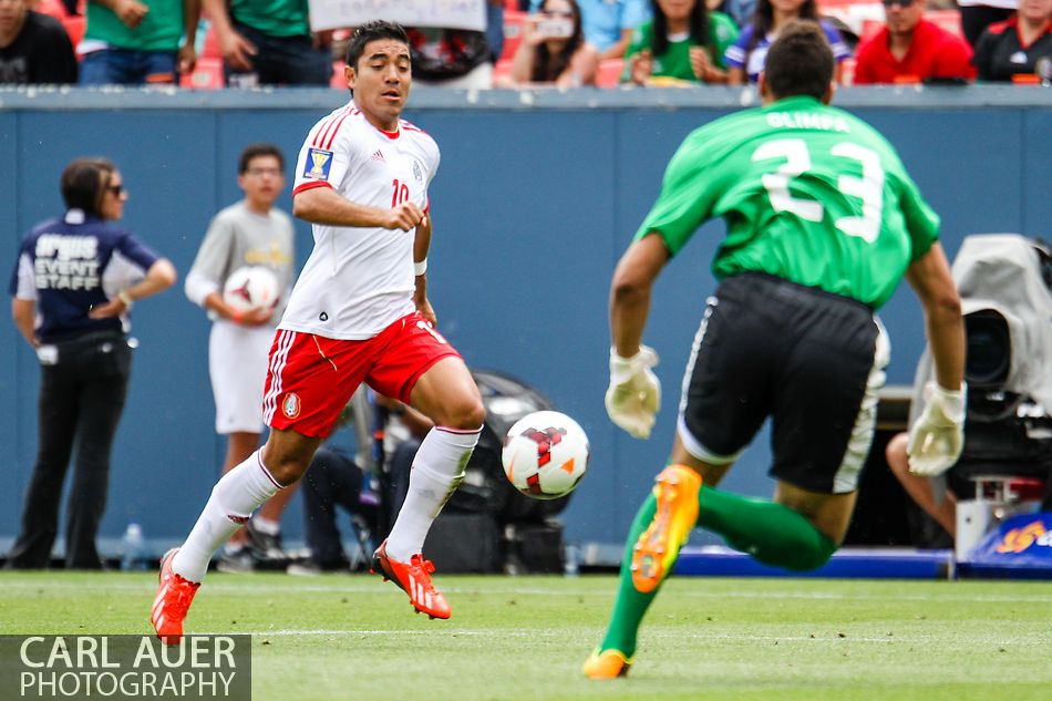 July 14 2013:  Mexico Forward Marco Fabian (10) attacks the charging Martinique Goalie Kevin Olimpa (23) during the first half of the CONCACAF Gold Cup soccer match between Martinique and Mexico at Sports Authority Field in Denver, CO. USA.