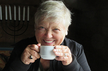 Author Pat Buschette drinking coffee and smiling