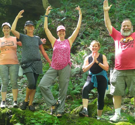 people hiking with arms raised in a yoga pose