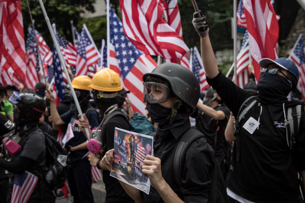 Image of protestors wearing protective gear and holding American flags